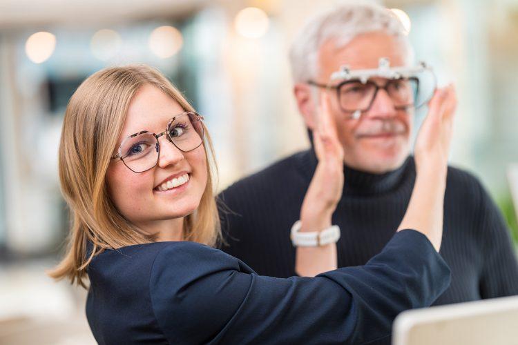 Augenoptikerin bei Sehanalyse mit Kunden