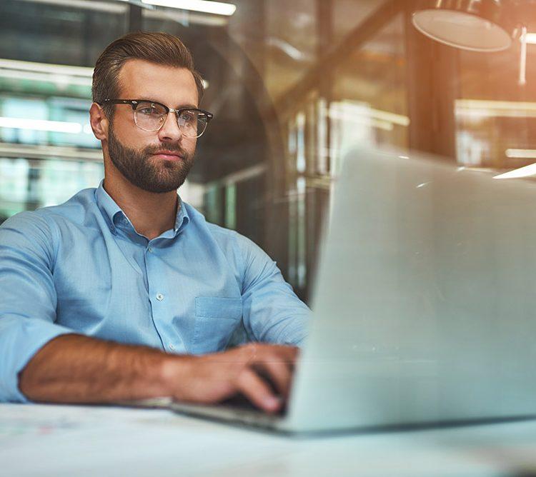 Mann am Laptop mit Brille