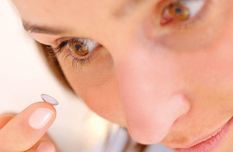 Frau hält Kontaktlinse vor ein Auge zum Einsetzen