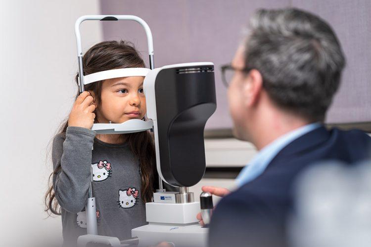 Kind wird vom Optiker auf Kurzsichtigkeit mit Lenstar geprüft